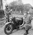 Military Police motorcyclists demonstrate how a metal rod fitted to a motorcycle can prevent the rider from being killed by a wire stretched across the road, 25 October 1944. B11247.jpg