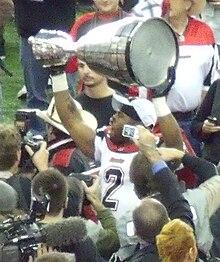Un jugador con uniforme blanco con ribete rojo y un número 2 negro en el pecho levanta un gran trofeo plateado sobre su cabeza.