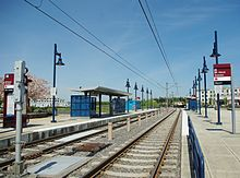 The side platforms of Mt. Hood Avenue station; the platforms consists of blue lamps and the left one contains a shelter