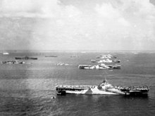 Black and white photograph of six aircraft carriers and other ships moored in rows