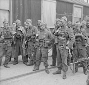 A group of 15 men in uniform carrying weapons