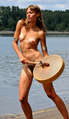 Nude woman standing on shore with drum.png