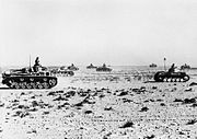 Several tanks advance to the right across the brush-covered desert.