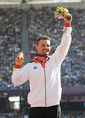 A Caucasian man with dark hair wearing a white zipped up top. He holds a bunch of flowers in his left hand, and clutches a gold medal in his right.