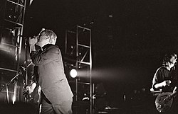A black-and-white photograph of Michael Stipe and Peter Buck performing on stage with spotlights on them. Stipe is to the left singing into a microphone, wearing a three-piece suit, he has bleach-blond hair and is obscuring Mike Mills, whose bass guitar is visible from behind him. Peter Buck is playing guitar and wearing a button-up pattern shirt behind Stipe to the photograph's right with a sneer on his face.