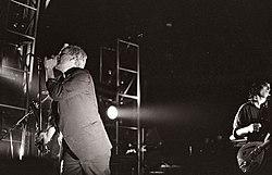 Nigrablanka foto de Michael Stipe kaj Peter Buck rezultanta sur scenejo per spotlumoj sur ili. Tigo estas maldekstren kantanta en mikrofonon, portante tripartan vestokompleton, li havas blankblondan hararon kaj obskuras Mike Mills, kies basgitaro estas videbla de malantaŭ li. Peter Buck ludas gitaron kaj portas tutbutonan padronĉemizon malantaŭ Stipe al la rajto de la foto kun rikano sur sia vizaĝo.