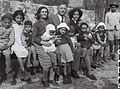 REPRESENTATIVES OF THE JEWISH AGENCY WITH A GROUP OF YEMENITE ORPHAN IMMIGRANT CHILDREN AT THE ATLIT RECEPTION CAMP. מחנה העולים בעתלית. בצילום, נציגיD822-020.jpg