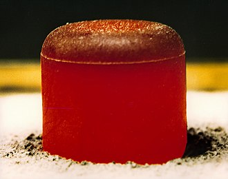 Radioisotope thermoelectric generator - A pellet of <sup>238</sup>PuO2 as used in the RTG for the ''Cassini'' and ''Galileo'' missions. This photo was taken after insulating the pellet under a graphite blanket for several minutes and then removing the blanket. The pellet is glowing red hot because of the heat generated by radioactive decay (primarily α). The initial output is 62 watts.