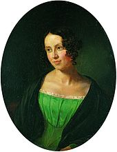 Portrait of a young lady, over a black background. She is wearing a green dress, over a black coat, she is looking to the left, somewhat smiling.