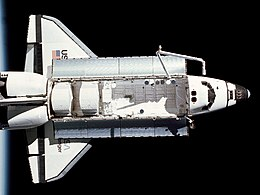 Top view of a spaceplane in space, with the horizon of Earth in the background.