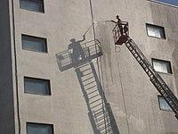 Shadow of man pressure washing a building.jpg