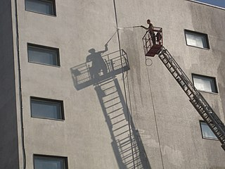 Shadow of man pressure washing a building.jpg