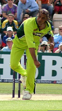 A man, in Pakistani national cricket team ODI uniform, just after delivering the ball.