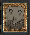 Sisters Lucretia Electa and Louisa Ellen Crossett in identical skirts, blouses, and jewelry with weaving shuttles LOC 5228567537.jpg