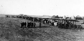 A slightly side-on ront view of a line of early aircraft on a flat piece of land. People are standing with the aircraft, with a group standing in front of the machines. Several tent-like structures can be seen in the background.
