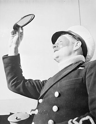 Merchant navy - A portrait of a New Zealand Merchant Navy captain of a Fairmile 'submarine chaser', as he holds it up and looks through a small coloured screen.  This disc allows him to look into the sky to search for dive bombers without damaging his eyes.