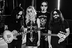 The Pretty Reckless in October 2014. From left to right: Ben Phillips, Taylor Momsen, Mark Damon, Jamie Perkins