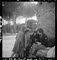 Toni Frissell, sitting, holding camera on her lap, with several children standing around her, somewhere in Europe LOC 6057154284.jpg