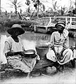 Two women with buckets seated at waterside (4291094182).jpg