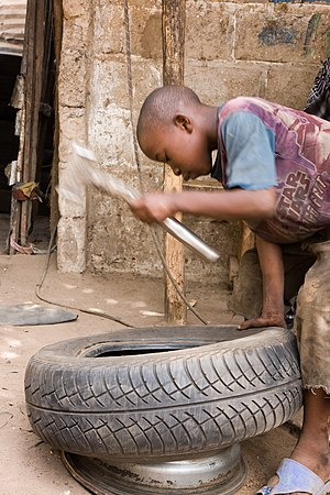 A kid repairs a tyre in The Gambia
