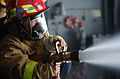 US Navy 031018-N-8295E-319 Rachel Vata, from Superior, Colo., mans a fire hose during a damage control demonstration held in the USS Ronald Reagan (CVN 76) hangar bay.jpg
