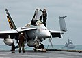 US Navy 041201-N-5345W-037 Plane Captains clean one of the squadron's F-A-18C Hornets on the flight deck of the Nimitz-class aircraft carrier USS Harry S. Truman (CVN 75) as the guided missile cruiser USS Monterey (CG 61) sails.jpg