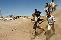 US Navy 050507-N-6501M-049 U.S. Navy Photographer's Mate 1st Class Steve Harbor runs along side Iraqi citizens as he documents them while they participate in a physical readiness test for selection to go to the Iraqi Police Tra.jpg
