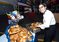 US Navy 060528-N-1371G-039 Culinary Specialist 3rd Class Siriphone Phakdy places fresh rolls on one of the reception tables set up in the hangar bay of the amphibious assault ship, USS Kearsarge (LHD 3).jpg