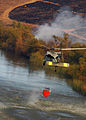 US Navy 071023-N-3069F-040 An MH-60S Seahawk assigned to Helicopter Sea Combat Squadron (HSC) 85, lifts a full 420-gallon extinguishing trough from a local reservoir near the raging wildfires in San Diego County.jpg