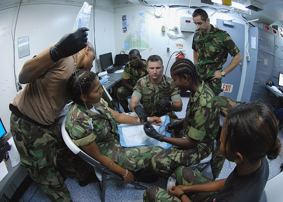 US Navy 080123-N-4044H-052 Chief Hospital Corpsman Chris Maurer demonstrates to Sao Tomain military personnel the procedure for inserting an intravenous drip into a person's vein