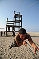 US Navy 080715-N-2959L-213 Seaman Apprentice Giovanny Magallon pulls himself along a rope while participating in an obstacle course.jpg
