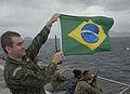 US Navy 090712-A-8397T-001 Brazilian Marine 1st Lieutenant Jose Sena holds up a Brazil flag aboard the amphibious dock landing ship USS Oak Hill (LSD 51) before arriving in Rio De Janeiro, Brazil.jpg
