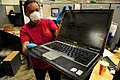 US Navy 100506-N-5862D-002 nformation Systems Technician 1st Class Latarsha Young displays one of many computers that were damaged by floodwaters at the Navy Recruiting Command storage annex.jpg