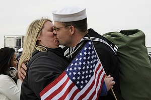 US Navy 111210-N-QO773-141 A Sailor kisses his wife upon return to home port.jpg