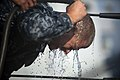 US Navy 120105-N-PB383-541 A Sailor pours water on his face after being sprayed with oleoresin capsicum.jpg