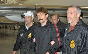 "A mustached man, looking at the camera, in a shiny black warmup jacket with red stripes walking between two men wearing black jackets with large gold badge-shaped patches, and white lettering on their sleeves and breasts. It says ""DE"" on the man on the right and ""DEA"" on the man on the left. Both men are holding the adjacent elbow of the man in the center. The man on the left is wearing a white baseball cap; part of an airplane and the walls of a hangar are visible in the background"