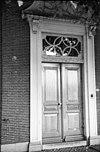 foto van Pand met lijstgevel, waarin een ingangspartij met hoofdgestel op consoles, waarboven twee gebeeldhouwde wapens. Gesneden dubbele deur, gesneden kalf en bovenlicht