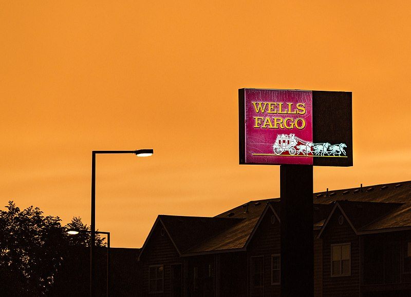 The deal seems a fitting end to an astounding series of mess-ups at Wells Fargo Tony Webster from Minneapolis, Minnesota, United States, Wells Fargo Bank Sign Sunset (28052532561), CC BY-SA 2.0