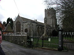 Stone building with arched window and square tower, separated from the road by a stone wall and railings.