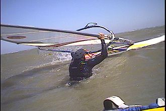 Boom (windsurfing) - A sailor is controlling the sail with one hand on the boom, and the other on the mast, preparing to waterstart.