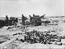 An artillery gun and its crew in a desert. A pile of shell cases is in the foreground.