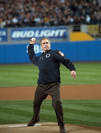 2001 World Series - Donning an FDNY fleece, with a bulletproof vest underneath, President Bush tosses out the ceremonial first pitch.