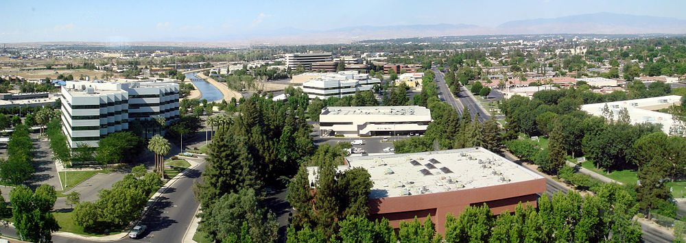 A panoramic view of Bakersfield, taken from Stockdale Tower, the tallest building in the city, facing east/northeast. The office buildings in the foreground make up a mini financial district and regional offices for many oil companies that operate in the region; the major street to their right is California Avenue. Towards the upper right is downtown Bakersfield, marked by the black-with-white-roof Truxton Tower (the 2nd tallest building in the city). The area rising in the background-right is East Bakersfield. The mountain range is the background are the Greenhorn Mountains.