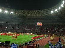 "The interior of a football stadium at night, lit by floodlights. Performers are on the field and the supporters in the far stand are holding up cards that read ""Believe"" in silver on a red background."