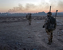 Colour photograph of marines patrolling in single file over rough, almost barren, terrain with buildings on the horizon.
