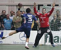6ccce5850f Um jogador arremessa à baliza durante uma partida de handebol.