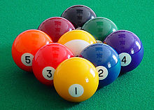 9 pool balls in a diamond shape on a pool table