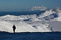 A hunter descends from a knoll near Lake Bonnie Rose, Great Sitkin Volcano in background. Adak Island, Aleutian Islands, Alaska.jpg