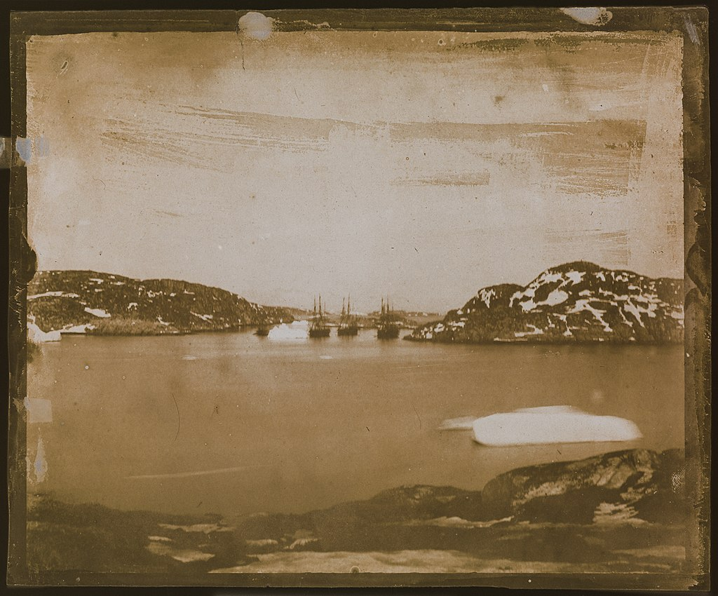a sepia toned photographic view of four ships in the distance sailing through a channel.