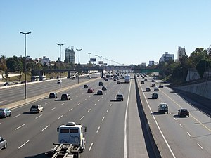 Local-express lanes - North Access freeway over National Route 9. The express lanes (left, all vehicles) and local lanes (right, cars and buses only) are clearly seen on this photo that shows the view towards the north, from the bridge on Melo street, at Florida, Vicente López, Buenos Aires Province, Argentina. Speed limit signs for each lane, indicating speed limits of 130, 120, 120, 110, 100 and 90 km/h, can be seen at the bridge. A bus priority lane can be seen at the right side of the yellow line in the local lane section.